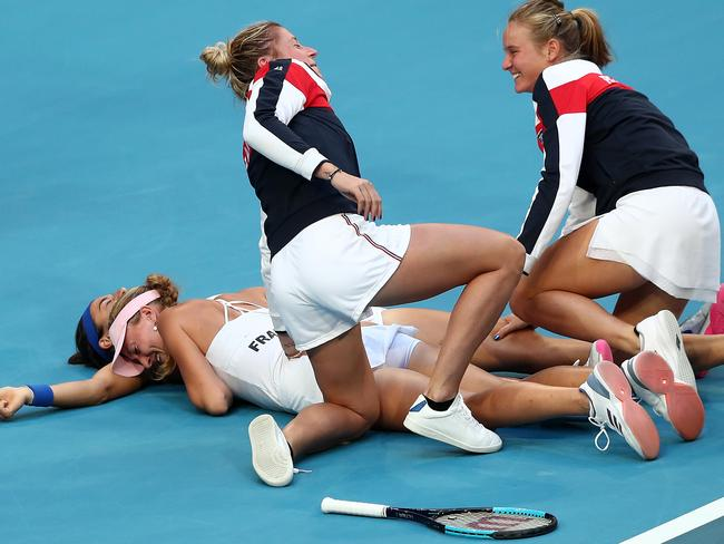 Kristina Mladenovic and Caroline Garcia celebrate after the doubles. (AAP Image/Gary Day)