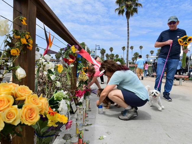 A woman places a flower at a makeshift memorial for the victims. Picture: Frederic J. Brown/AFP