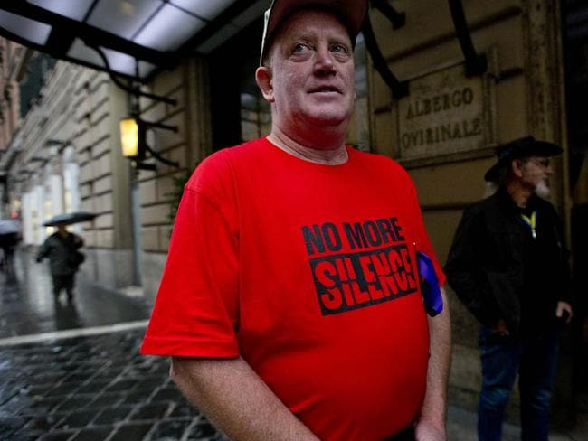 """Dominic Ridsdale, a survivor of priestly sex abuse, wears a shirt reading """"No more silence"""" as he stands in front of the Quirinale hotel in Rome. Picture: AP/Alessandra Tarantino"""