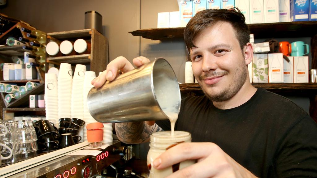 Cafes and restaurants will be able to reopen after no new cases for two complete incubation cycles. Izak Fogarty at Alcove Cafe and Deli, Wilston. Picture: AAP/Steve Pohlner