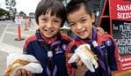 MELBOURNE, AUSTRALIA - NewsWire Photos December 5 2020: Boy Scouts Casey Hungerfield, 6 and Louis Lai, 6, get into a sausage in bread at Bunnings in Maribyrnong on Saturday morning as the Bunnings sausage sizzle is finally making a return in Melbourne after an eight-month absence. Picture: NCA NewsWire / David Geraghty