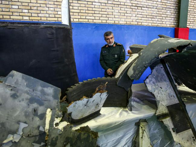 General Amir Ali Hajizadeh (C), Iran's Head of the Revolutionary Guard's aerospace division, looks at debris from a downed US drone. Picture: AFP