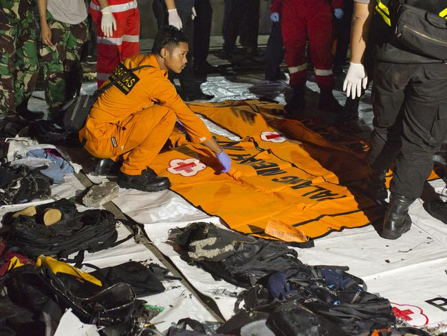 Search and rescue workers sits near a body bag and personal belongings of victims of Lion Air flight JT 610. Picture: Ed Wray/Getty Images