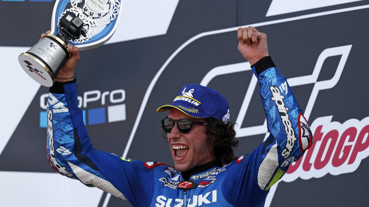Alex Rins holds up the trophy on the podium as he celebrates victory at Silverstone.
