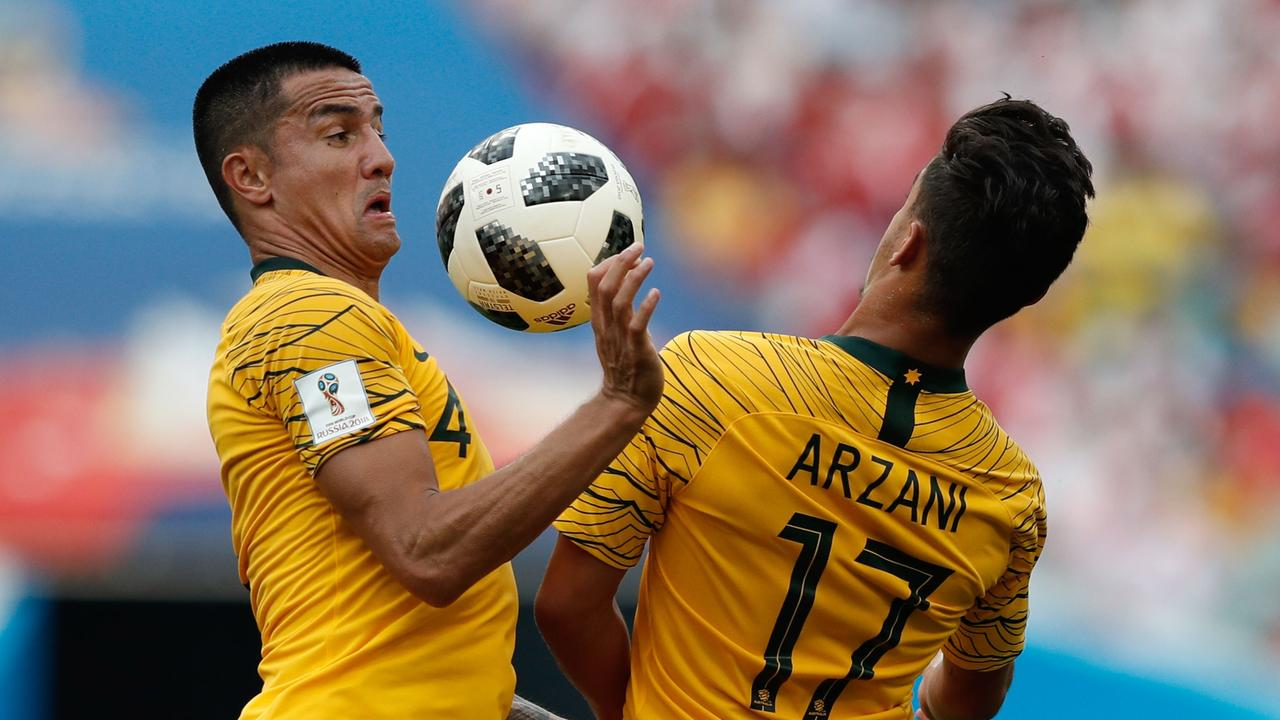 TOPSHOT - Australia's forward Tim Cahill (L) and Australia's forward Daniel Arzani go for the ball