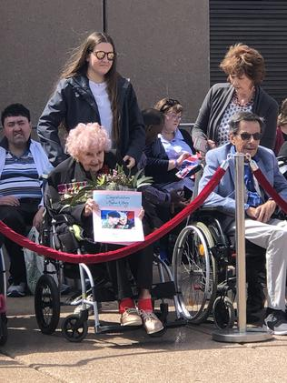 Holding a best wishes message for Prince Harry and Meghan Markle, Daphne Dunne has scored a prime spot at the Opera House today as she waits for her third royal greeting.