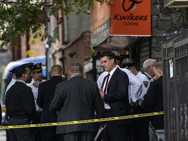 NYPD investigates the shooting scene in the Brooklyn borough of New York. Picture: AP