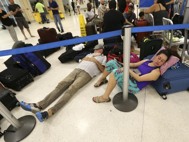 Travellers left stranded by Hurricane Maria sleep on the floor of the main international airport in San Juan, Puerto Rico. Picture: AP Photo/Gerald Herbert