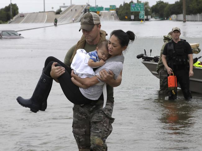 Houston Police SWAT officer Daryl Hudeck carries Connie Pham and her 13-month-old son Aiden to safety after rescuing them from their home. Picture: AP