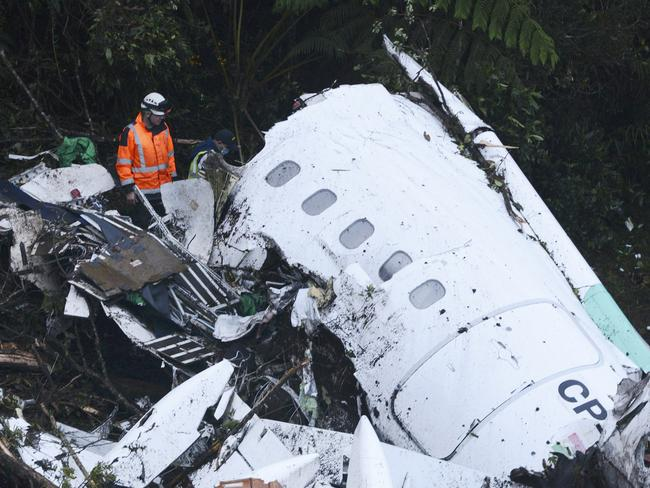 Rescue workers search at the wreckage site of the chartered plane that crashed outside Medellin, Colombia.