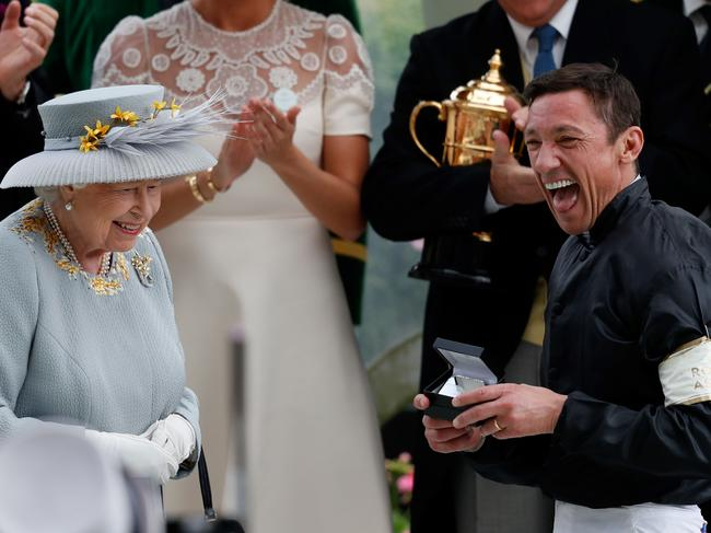 The Queen shares a smile with champion jockey Frankie Dettori after he won the Gold Cup on horse Stradivarius, his fourth win of the day. Picture: AFP