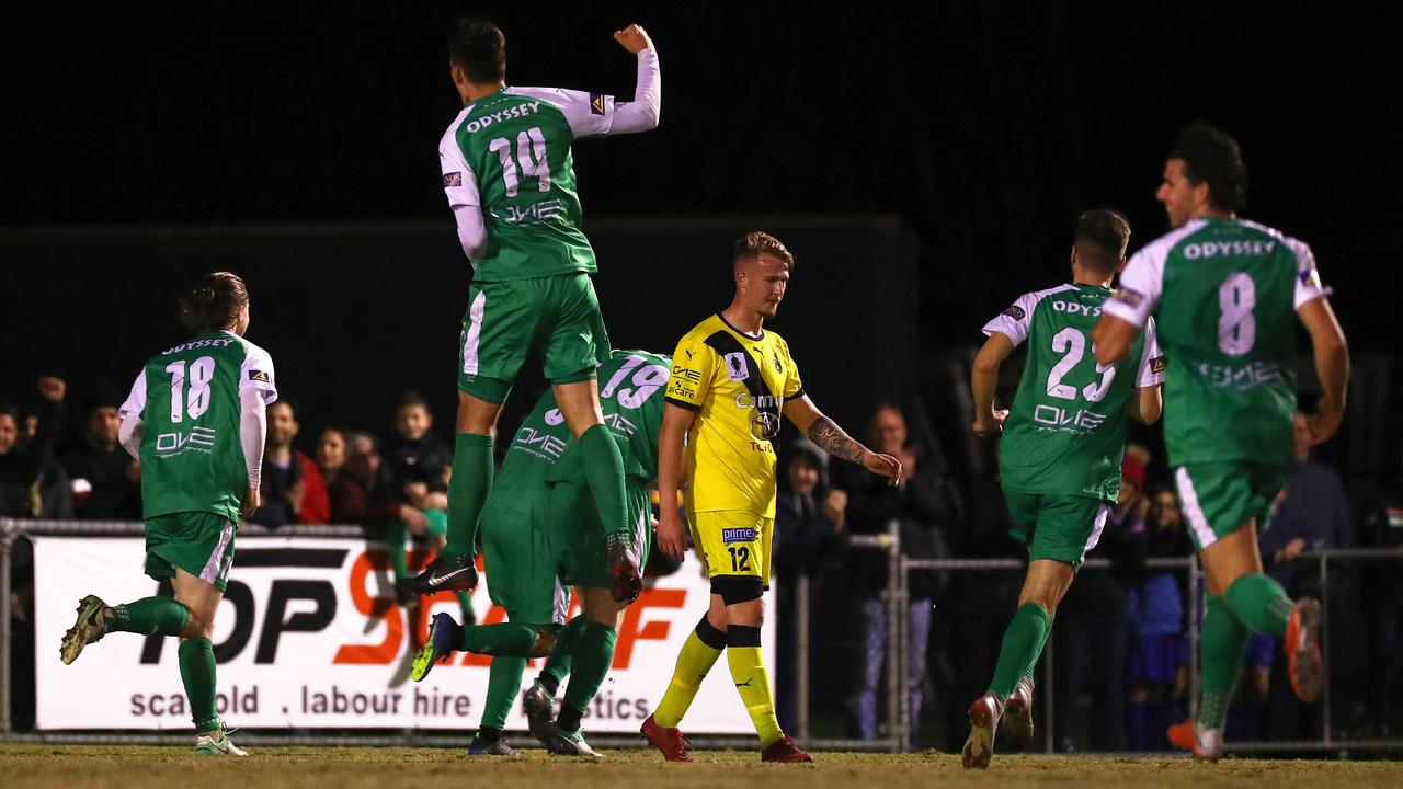 Harvey Read of Heidelberg United (centre) walks away after Jacob Alexander of Bentleigh Greens scores his goal