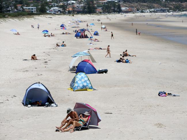 Beachgoers keep cool at Brighton on Monday. Picture: AAP / Kelly Barnes