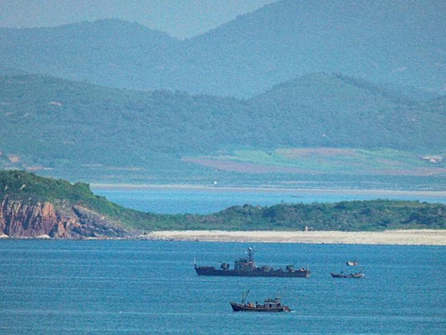 A tiny North Korean fishing vessel is dwarfed by a North Korean coast defence ship off North Korea's Hwanghae province.
