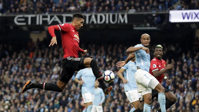 Manchester United's Chris Smalling, left, scores his side's third goal