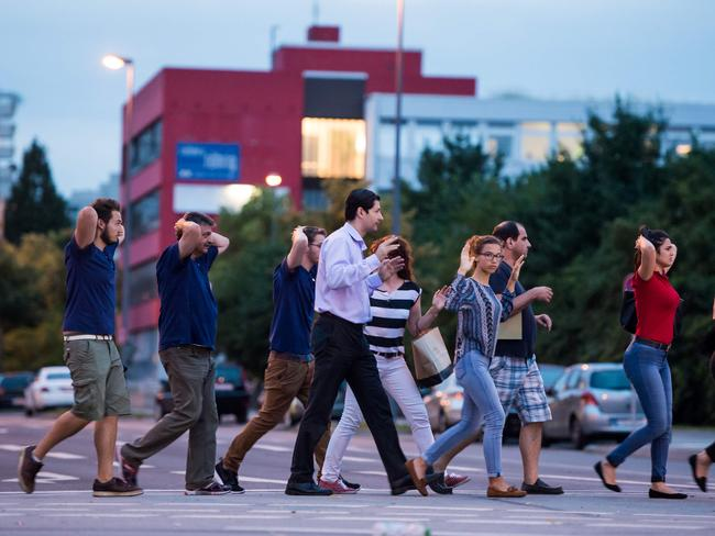 Evacuated people from the shopping mall walk with their hands up. Picture: AFP