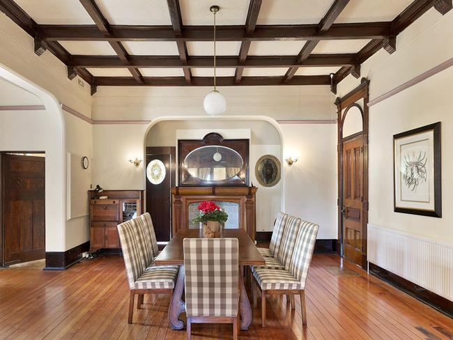 The dining room has mahogany beamed ceilings and oversized panel doors.