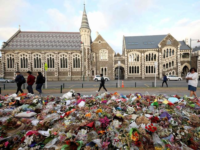 People walk past flowers and tributes displayed in memory of the twin mosque massacre victims outside the Botanical Gardens in Christchurch. Picture: AFP