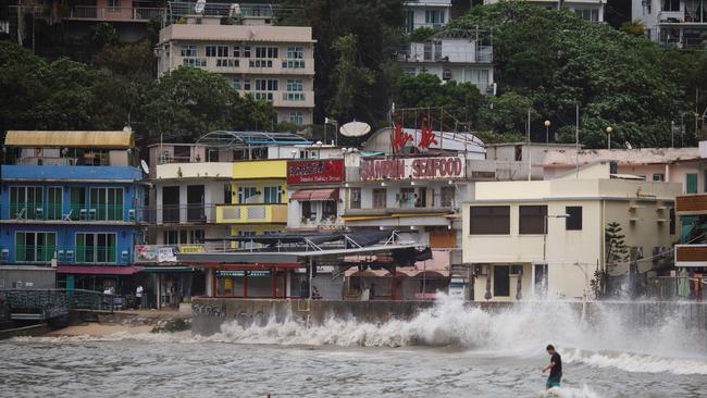 A man walks out on a low-lying wharf as large waves caused by Typhoon Hato break along the waterfront in Hong Kong's Lamma Island. Picture: AFP/Bahar Tengku