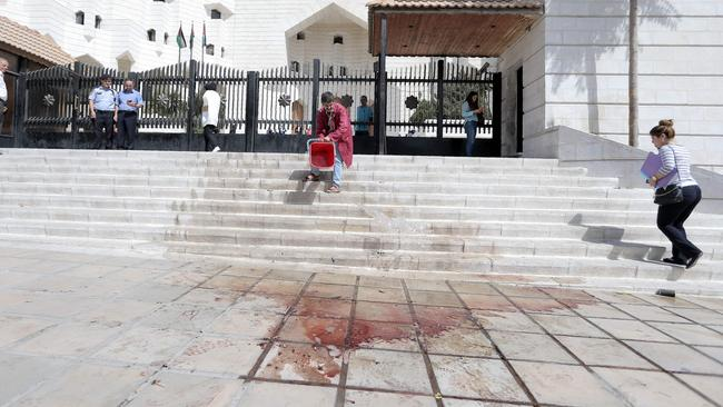 A man cleans the blood of prominent Jordanian writer Nahed Hattar after he was shot dead outside a court in Amman where he was facing charges for sharing a cartoon deemed offensive to Islam. Picture: AFP/Ahmad Alameen