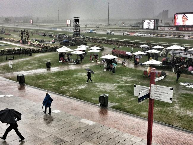 Heavy rain sent crowds running for cover. Picture: George Salpigtidis