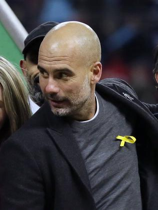 Manchester City's manager Pep Guardiola wears a yellow ribbon on his jumper during the celebrations after his side won the English League Cup Final