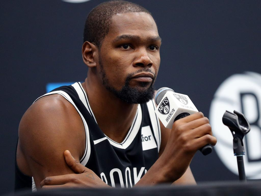 """(FILES) In this file photo taken on September 26, 2019 Kevin Durant #7 of the Brooklyn Nets speaks to media during Brooklyn Nets Media Day at HSS Training Center on September 27, 2019 in the Brooklyn Borough of New York City. - Kevin Durant is among the four Brooklyn Nets players to test positive for the coronavirus, he told The Athletic on March 17, 2020. """"Everyone be careful, take care of yourself and quarantine,"""" Durant told The Athletic, adding that he is feeling fine and not showing any symptoms. """"We're going to get through this."""" The Nets did not identify any players and said Tuesday that of the four players, only one is exhibiting symptoms. All four are isolated and are undergoing medical care from team physicians, the Nets said in a statement. (Photo by Mike LAWRIE / GETTY IMAGES NORTH AMERICA / AFP)"""