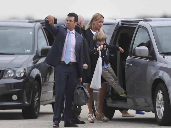Donald Trump Jr. centre, stops to take a photograph with his phone during his family's arrival at Andrews air force Base, as Vanessa Trump picks up their son Spencer to place him in the mini-van. Picture: AP