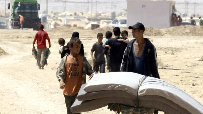 Young Syrian refugeestransport mattresses through the Zaatari refugee camp. Picture: AP