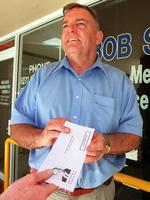 Bob Such handing out questionnaire asking his electorate which party they would prefer him support as an independent member of Parliament in 2002.
