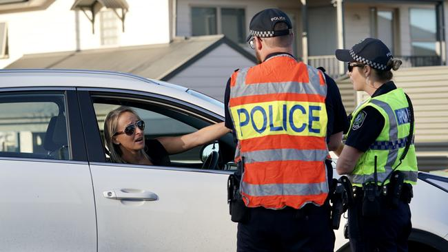 Police speak to a woman driving past. Picture: Mike Burton/AAP
