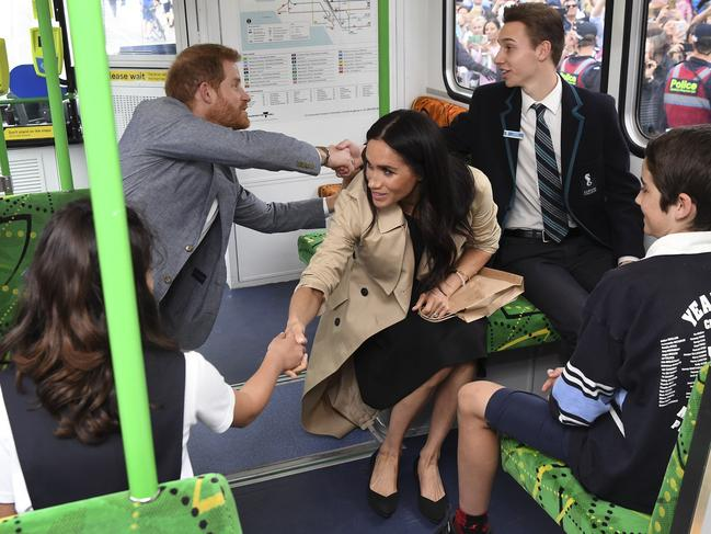 Britain's Prince Harry and his wife Meghan, Duchess of Sussex shake hands with local schoolchildren as they take a ride on a tram in Melbourne. Picture: AFP