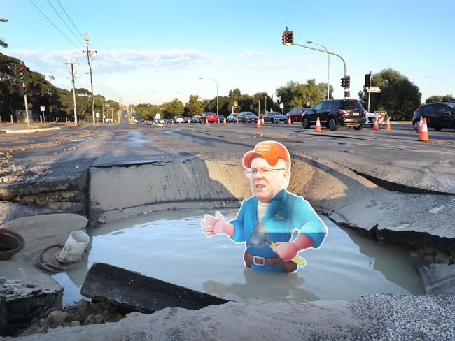 Substitute Ian in the deep hole caused by a burst water main on Grand Junction Rd. Picture: Dean Martin