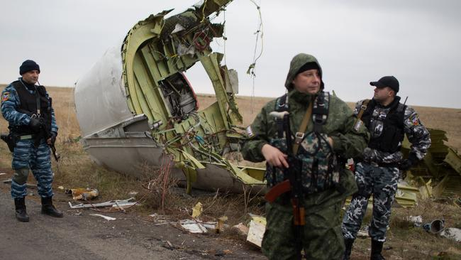 Pro-Russian gunmen stand guard as Dutch investigators (unseen) arrive near parts of the Malaysia Airlines Flight MH17 at the crash site near the Grabove village in eastern Ukraine on November 11, 2014, hoping to recover debris from MH17. Picture: Menahem Kahana.