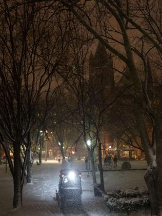 A plough clears Church Square Park as snow falls during the start of a heavy winter storm January 26, 2015 in Hoboken, New Jersey.