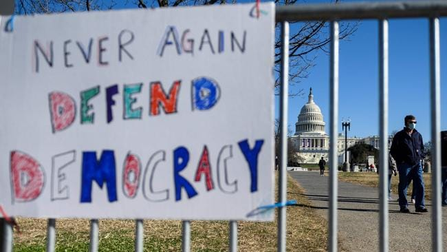 People pass signs of support in Washington following the storming the Capitol. Picture: Andrew Caballero-Reynolds/AFP