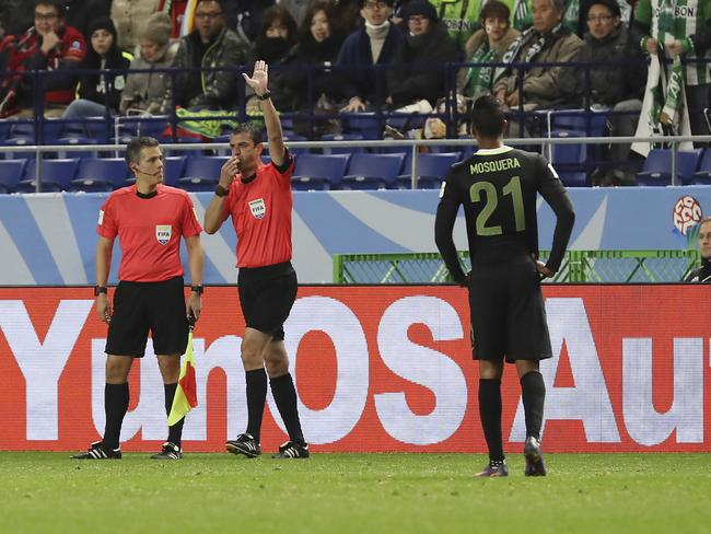 Referee Viktor Kassai, second left, blows his whistle after checking with the video assistant referee.