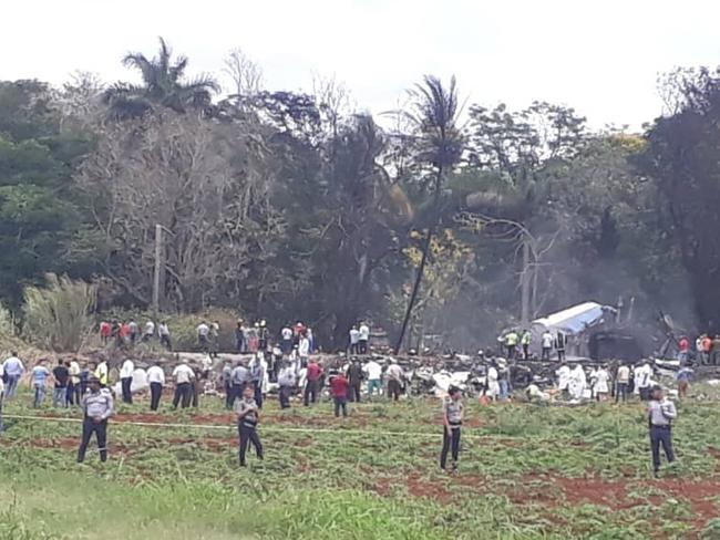 Rescue and search workers on the site where a Cuban airliner with 104 passengers on board plummeted into a yuca field just after takeoff from the international airport in Havana, Cuba. Picture: Andrea Rodriguez