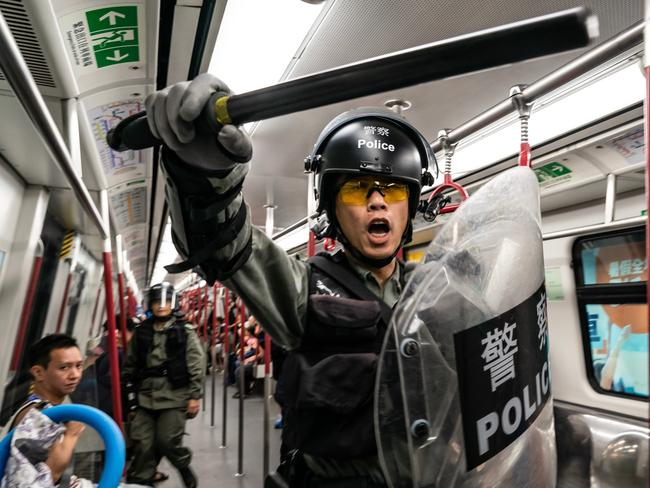 Riot police charge in a train at the Tung Chung MTR station after protesters block the transport routes to the Hong Kong International Airport. Picture: Anthony Kwan/Getty Images