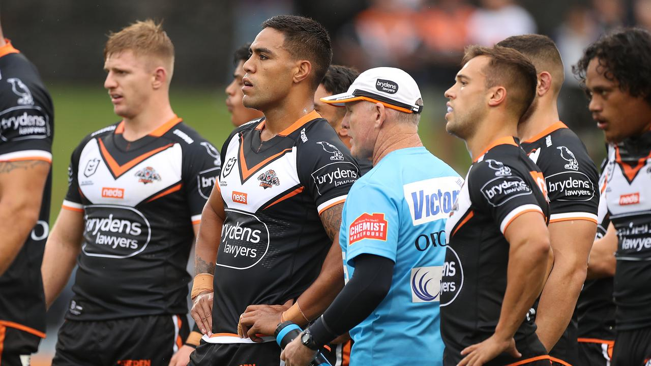 Tigers players look on after conceding a try against the Roosters.