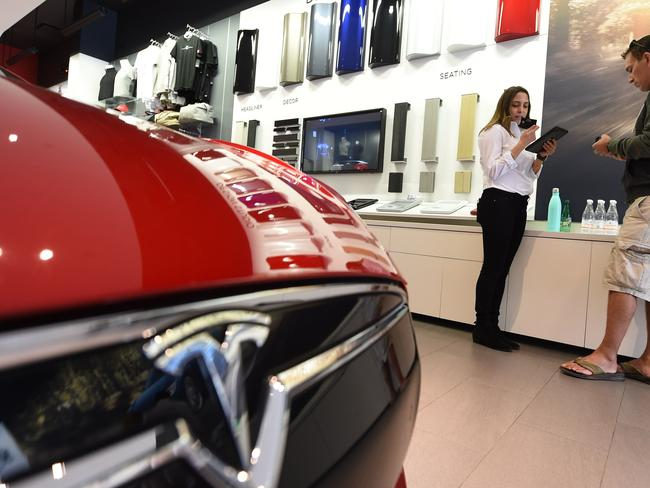 A sales representative (L) helping a customer pre-order, the as yet unseen Tesla Model 3, in the Tesla store in Santa Monica, California. Picture: AFP