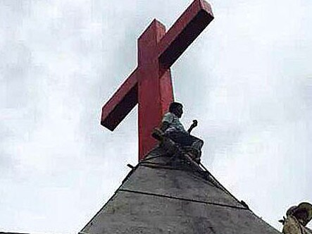 A church member attempts to protect a cross on the roof of a Protestant church in Wenzhou after Communist Party officials moved to seize the property.