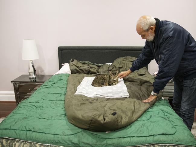 David Tonkin pets Ned, his son Matthew's cat, that now sleeps on David's bed on the sleeping bag Matthew used in Afghanistan, in Perth, Australia. Picture: AP Photo/David Goldman.