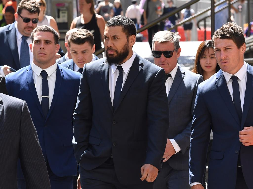 Canterbury Bankstown Bulldogs NRL players Adam Elliott (second left), Asipeli Fine (centre) and team captain Josh Jackson (right) leave the Downing Centre Court following an adjournment in Sydney, Monday, December, 17, 2018. Elliott are Fine are charged with wilful and obscene exposure during Mad Monday celebrations. (AAP Image/Dean Lewins) NO ARCHIVING