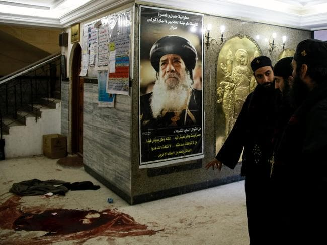 Blood stains on the floor next to a poster of the late Pope Shenouda III of Alexandria following the massacre. Picture: AFP/Samer Abdallah