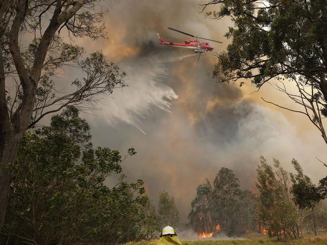 A water bombing helicopter attacks a bushfire near houses along Old Bar road in Old Bar, NSW, Saturday, November 9, 2019. Two people have been killed and seven others are missing in bushfires in NSW which have also destroyed at least 100 homes. (AAP Image/Shane Chalker)