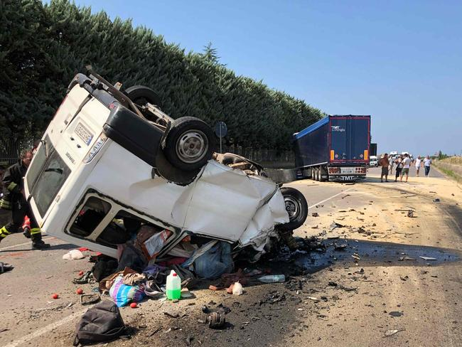 People stand at the site where a van smashed into a truck killing 12 migrant workers on-board near Foggia in southern Italy. Picture: AFP