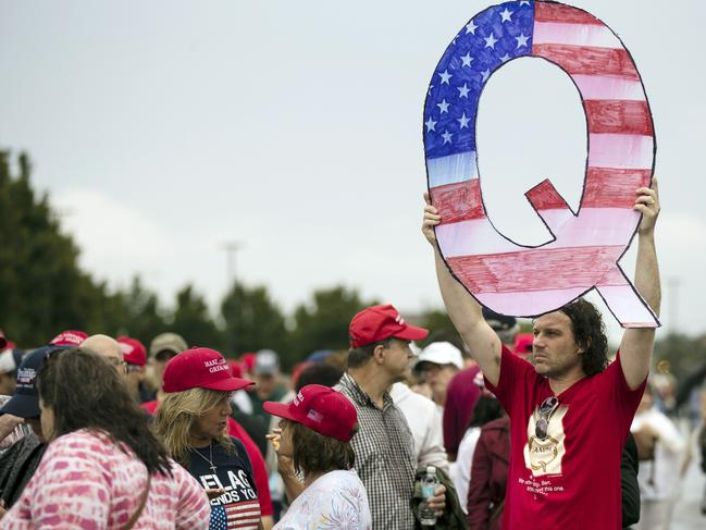 David Reinert holding a Q sign waits in line with others to enter a campaign rally with President Donald Trump in 2018. Picture: AP Photo/Matt Rourke, File.