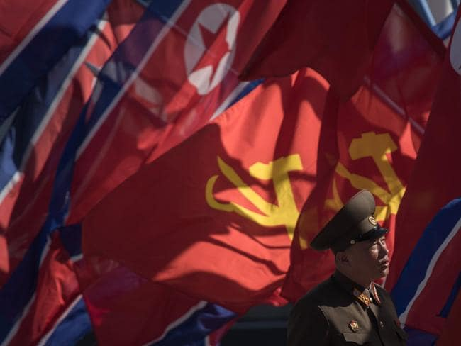 A Korean People's Army (KPA) soldier stands before flags prior to the opening ceremony for the Ryomyong Street housing development in Pyongyang. Picture: Ed Jones/AFP