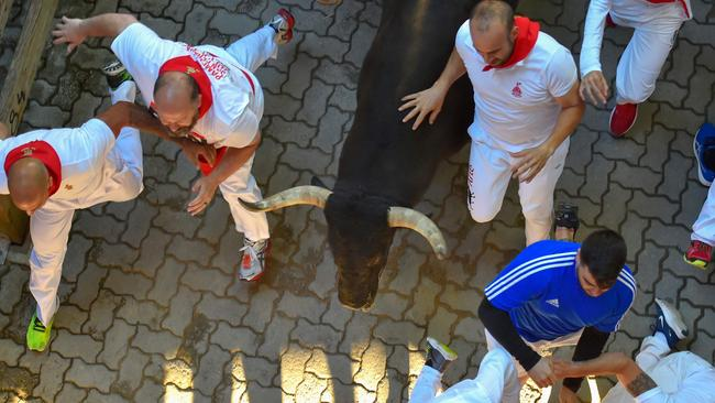 Participants run next to a fighting bull on the sixth bull run of the festival. Picture: AFP
